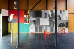 """Pavillon Le Corbusier, Ausstellung """"Le Corbusier und die Farbe"""", Evokation der mehrfarbigen Wandarbeit im Direktionszimmer, Usine Claude et Duval, Saint-Dié-des-Vosges FR, 1946–1950. Aneinanderstossende Farbflächen und Schwarz-Weiss-Reproduktion des puristischen Gemäldes """"Nature morte aux nombreux objets"""", 1923 (Ausschnitt). Stühle von Jean Prouvé aus der Serie """"Standard"""", lackiert in der Farbe """"Rouge Corsaire"""". Foto: Umberto Romito und Ivan Suta, 2021, Museum für Gestaltung Zürich / ZHdK"""