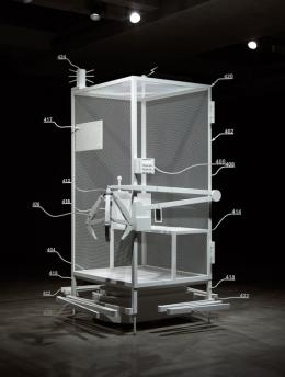 """Simon Denny, Amazon worker cage patent drawing as virtual King Island Brown Thornbill cage (US 9,280,157 B2: """"System for transporting personnel within an active workspace"""", 2016), 2019, White matt powder coated stainless steel, steel, aluminium and MDF panels, plastic wheels, 120 x 100 x 270 cm, Photo: Jesse Hunniford / MONA"""