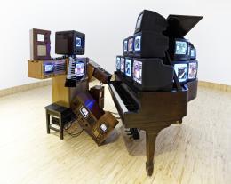 Nam June Paik Duet Memory, 1995 Videoinstallation (1 Klavier, 1 Laser-Disk-Player, 22 Fernseher in unterschiedlicher Größe, Radio- und Fernsehschränke, Holzbank, Hosenträger, Armbanduhr) Albertina, Wien. Sammlung Essl © Nam June Paik