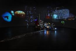 """Sarah Sze, """"Flash Point (Timekeeper)"""", 2018, Mixed Media Installation, Holz, Edelstahl, Videoprojektoren, Acryl, Archiv-Pigmentdrucke, Keramik und Klebeband © Sarah Sze"""