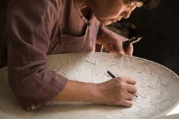 Meisterin Yang Jianqin bei der Anfertigung eines feinen Schnitz- und Ritzdekors. Motiv: Blätter. Foto: Franca Wohlt, 2018.